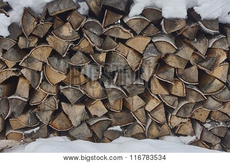 stack of firewood under snow. birch firewood. close up.