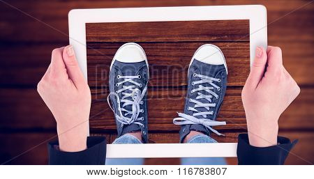 Feminine hands holding tablet against overhead of wooden planks