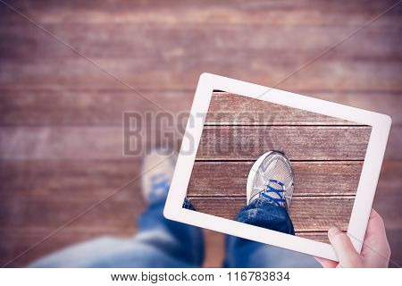 Masculine hand holding tablet against wooden planks background