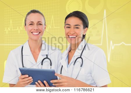 Nurses with tablet pc against medical background with ecg line in yellow