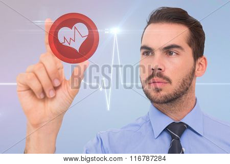Businessman measuring something with his fingers against medical background with green ecg line