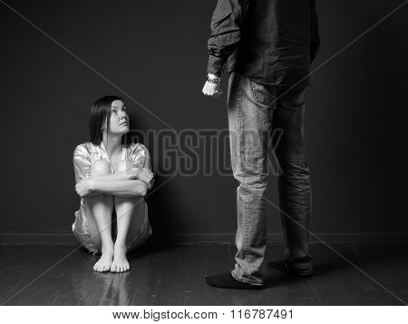 Sad Woman Is Sitting On The Floor, Standing Man's Figure  Threaten Her