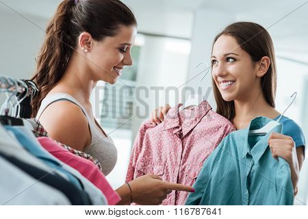 Girl shopping a choosing a shirt at the store a young smiling sales clerk is helping her