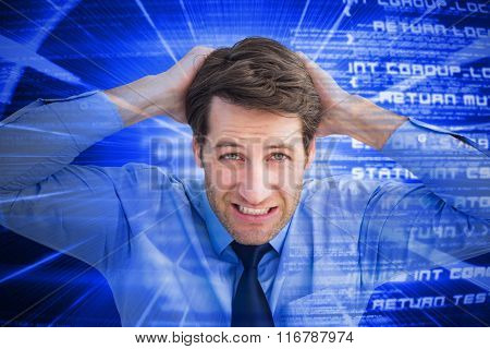Stressed businessman with hands on head against blue background with coding