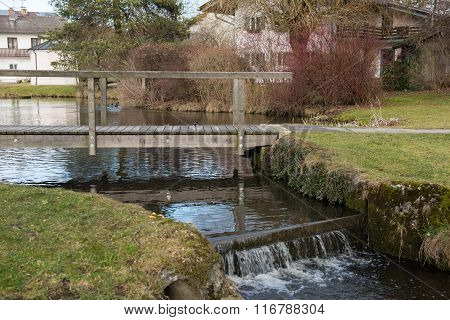 Pond With Bridge And Cascade In Bavaria