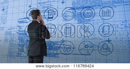 Handsome businessman looking against blue matrix and codes