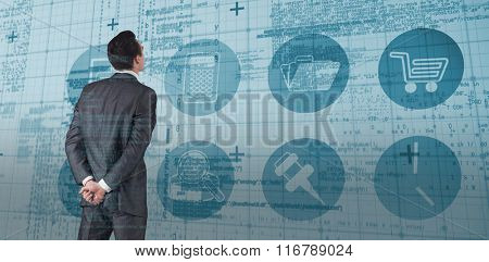 Businessman in grey suit looking against blue matrix and codes
