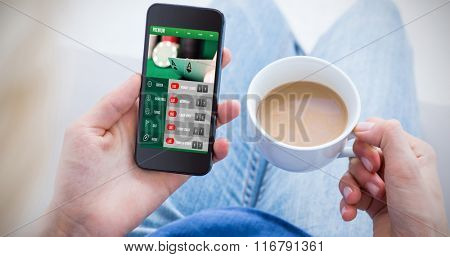 Woman using her mobile phone and holding cup of coffee against gambling app screen