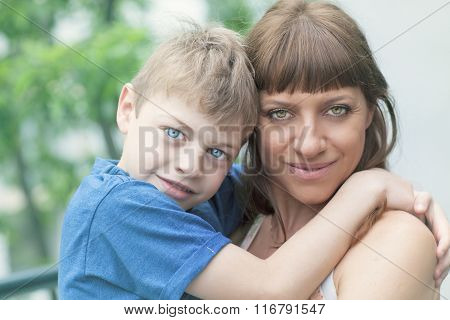 Portrait of an adorable boy hugging her mother