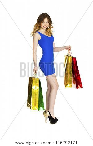 Full portrait of smiling young blonde girl with colorful shopping bags in blue dress posing on a white background