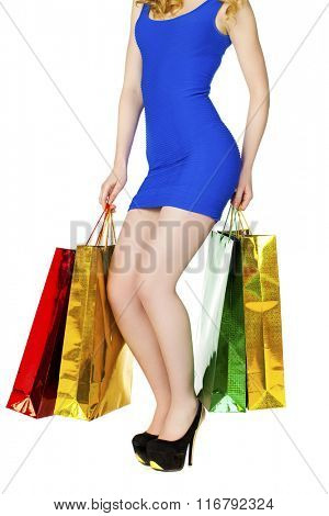 Body part sexy legs, girl with colorful shopping bags in blue sexy dress posing on a white background