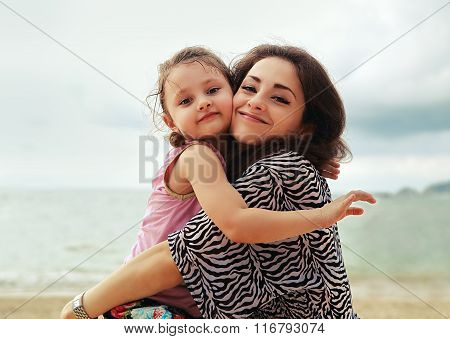 Happy Mother And Kid Girl Hugging With Natural Emotion Smiling On Blue Sea Backround