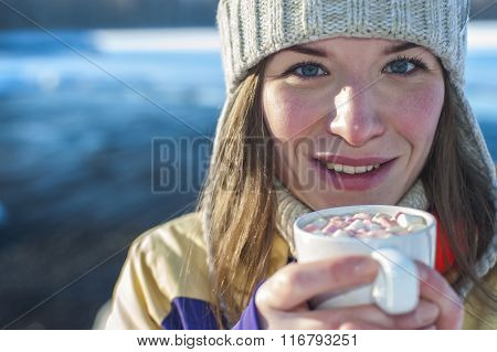Smiling Woman holds white cup of coffee with marshmallows.