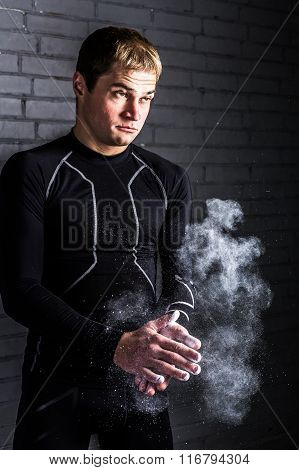 Portrait athlete rubbing his hands magnesia