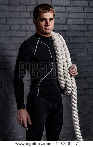 Man with twisted sport rope on shoulder