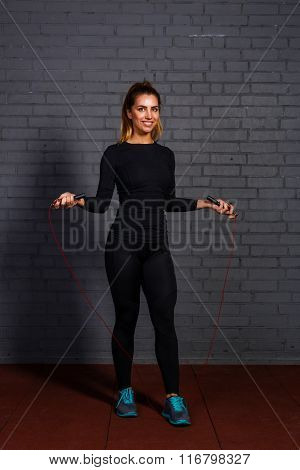 Smiling young woman posing with skipping rope