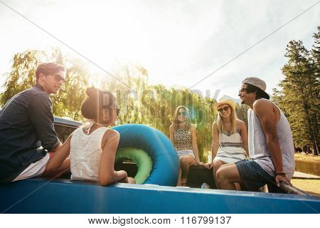 Group Of Young Friends Sitting In The Back Of A Pickup