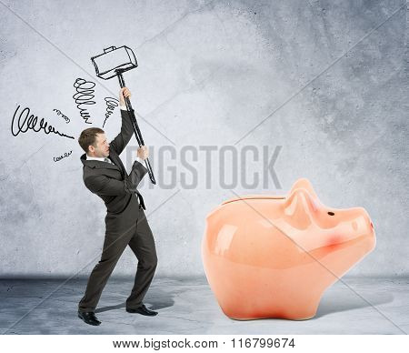 Businessman with hammer and piggy bank