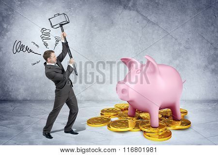 Businessman with hammer and piggy bank on coins