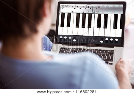 Pregnant woman using her laptop against music app