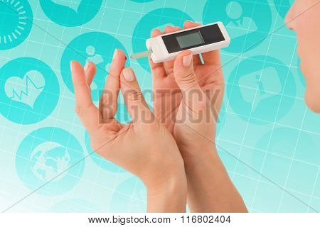 Diabetic woman using blood glucose monitor against ecg line on blue grid
