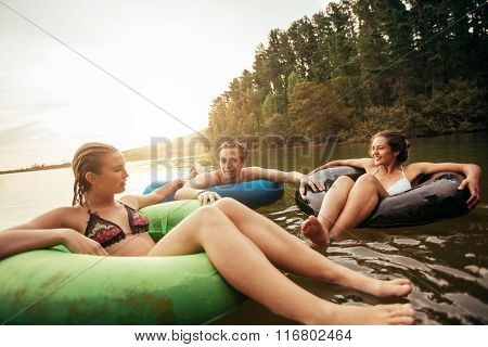 Friends Floating On Lake With Inflatable Rings