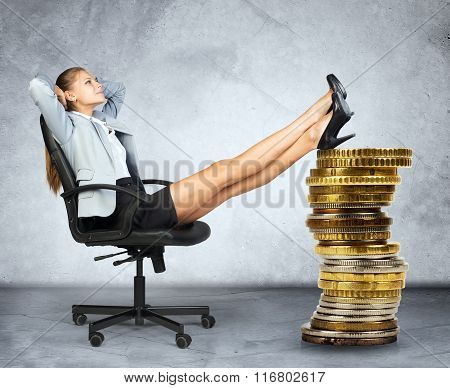 Businesswoman sitting on chair and pile of coins