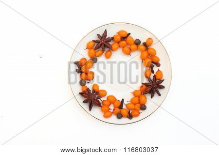 Round frame of Frozen sea buckthorn, cloves, star anise, black pepper on a white saucer on a white b