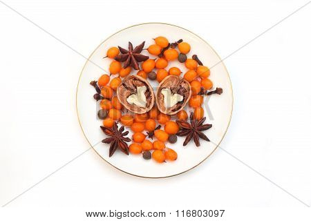 Frozen sea buckthorn, cloves, star anise, black pepper, walnut  halves on a white saucer on a white