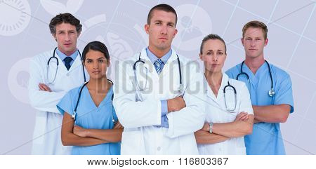Portrait of serious doctors standing with arms crossed against pastel blue