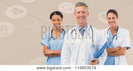 Portrait of male doctor with female staffs against beige background