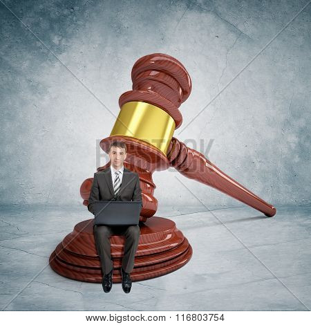 Businessman working on laptop with gavel