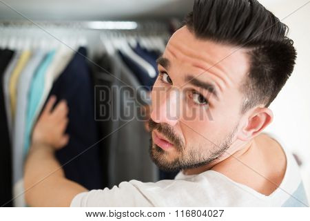 Man Tired Of Choosing Clothes During Shopping
