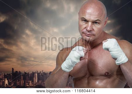 Portrait of man with fighting stance against dusty path leading to large city
