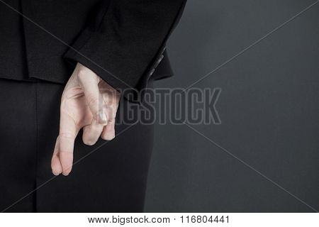 Rear view of businesswoman with fingers crossed behind her back against grey background