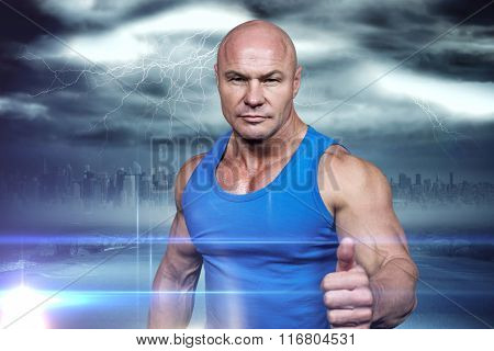 Portrait of confident muscular man showing thumbs up against stormy sky with tornado over road