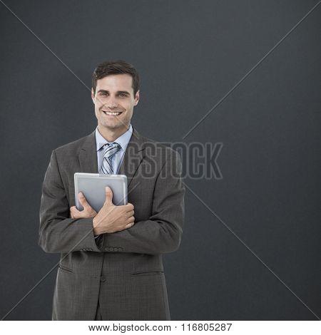 Portrait of smiling businessman holding digital tablet against grey background