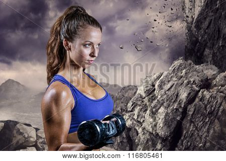 Side view of fit woman lifting dumbbell against rock crashing down from cliff