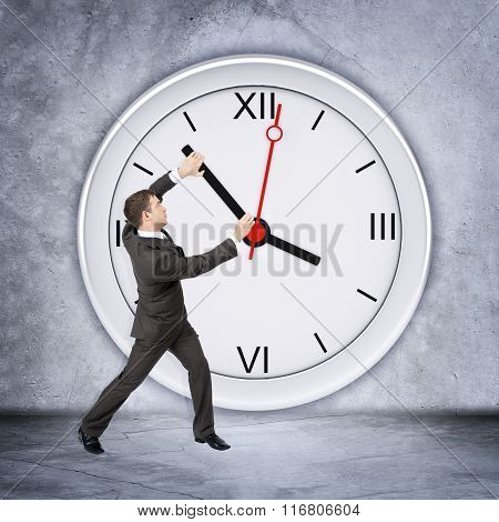 Businessman holding clock hand