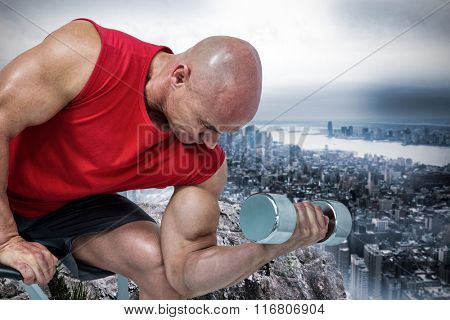 Bald man exercising with dumbbells while sitting on bench press against large rock overlooking huge city