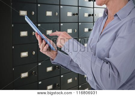 Businesswoman using her tablet against wall of black lockers