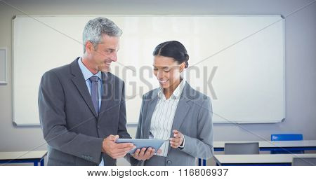 Business people using tablet computer against white board in a classroom