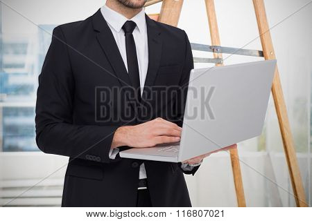 Mid section of a businessman using laptop against business stuffs laying on wooden scale