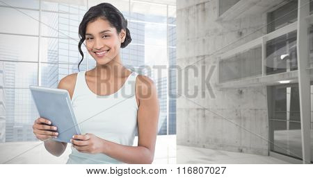 Portrait of smiling businesswoman using tablet computer against modern room overlooking city