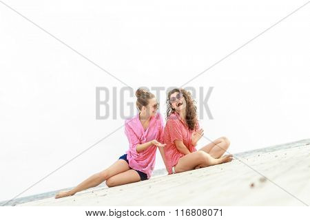 outdoor portrait of two young happy girls on tropical sea background, holiday image