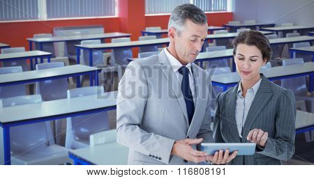 Business people looking at tablet against chair and table in a classroom
