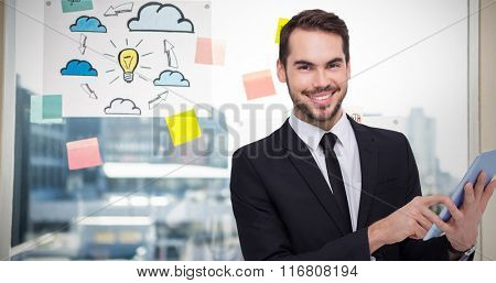 Businessman using his tablet while looking at the camera against adhesive notes on window