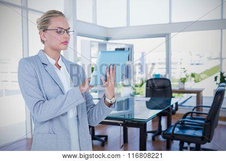 Businesswoman using digital tablet against board room