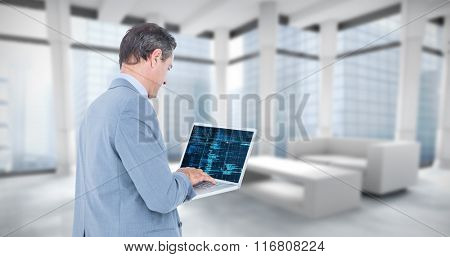 Businessman using laptop against modern room overlooking city