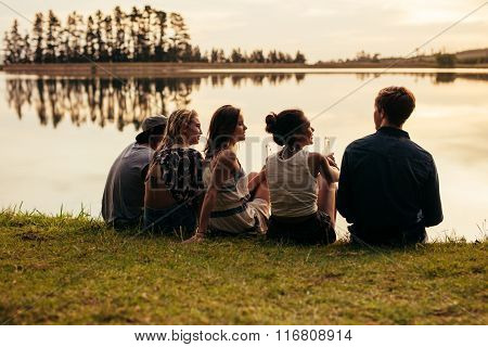 Group Of Young Friends Relaxing By A Lake